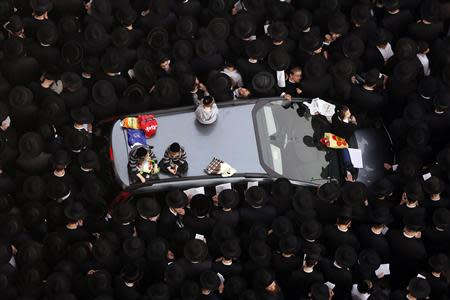 Ultra-Orthodox Jewish men stand around a car during a mass prayer in Jerusalem March 2, 2014. REUTERS/Darren Whiteside