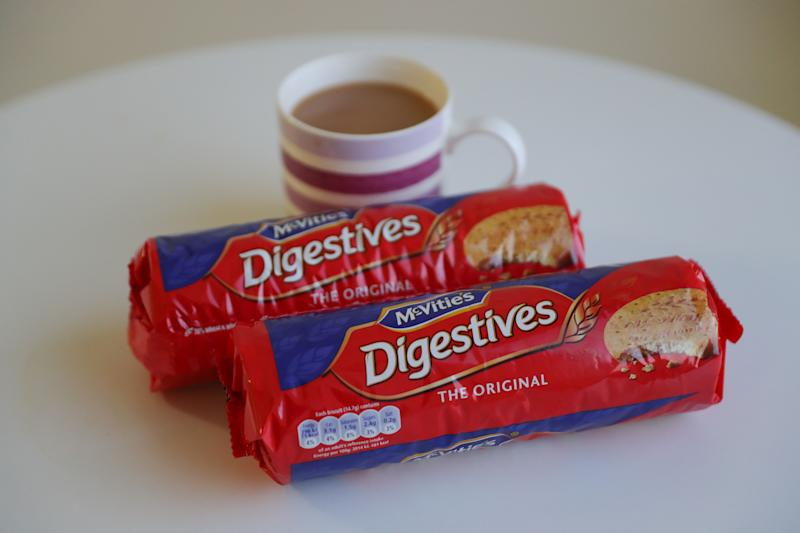 Two 400g packets of McVitie's Digestive biscuits are displayed beside a cup of tea, in London on January 19, 2018. A much-loved British biscuit has fallen victim to the Brexit-linked slump in the pound, as McVitie's Digestives on Friday said their packets will shrink. Packets of the quintessentially British brand will be cut from 500 to 400 grammes this month, after the weakened pound ramped up import costs. / AFP PHOTO / Daniel LEAL-OLIVAS (Photo credit should read DANIEL LEAL-OLIVAS/AFP via Getty Images)