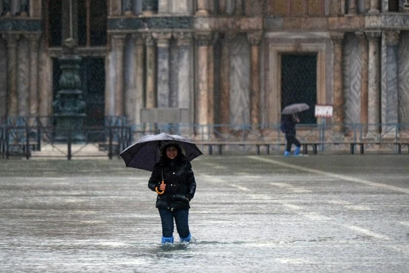 A tourist pose in St. Mark's Square after days of severe flooding in Venice