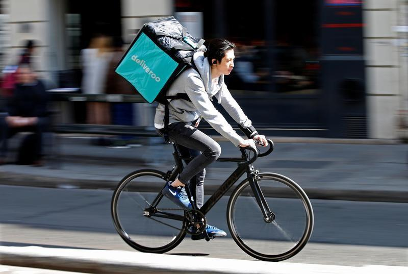 A cyclist rides a bicyle as he delivers food for Deliveroo, an example of the emergence of what is known as the 'gig economy', in Paris