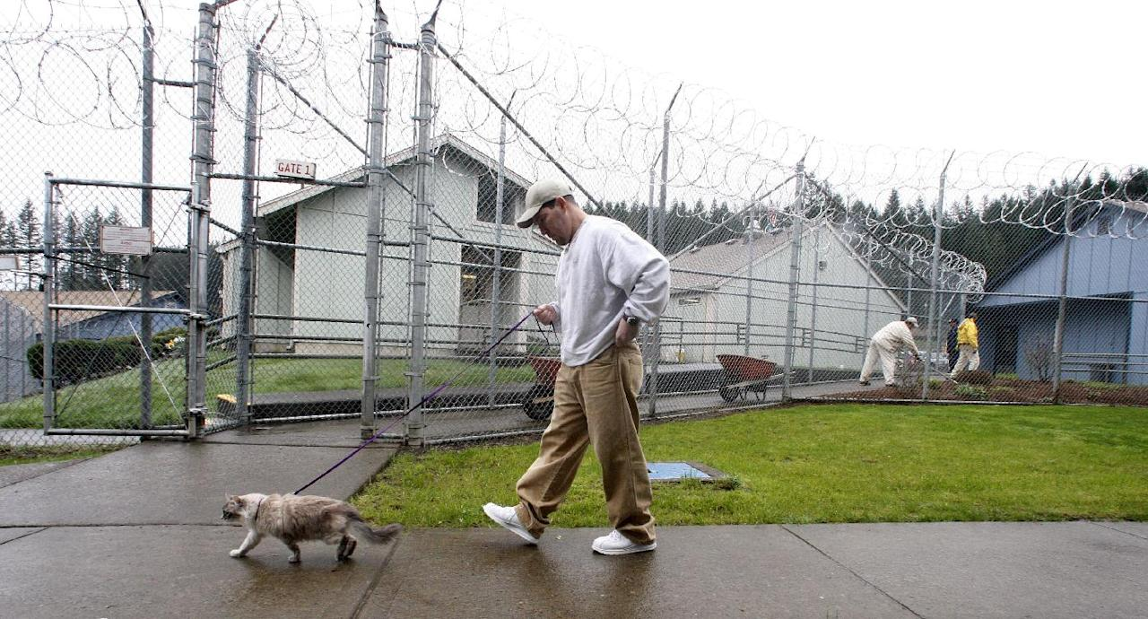 Inmate Richard Amaro walks Clementine at Larch Correctional Facility Friday, April 20, 2012, in Yacolt, Wash. The Cuddly Catz program at the Larch Correctional Facility, a minimum-security prison is several months old, but inmates say they've already noticed a difference in the cats and themselves. The program began in cooperation with a local animal shelter. It has grown to include two cats and four inmates, and the prison plans to add four more cats. (AP Photo/Rick Bowmer)