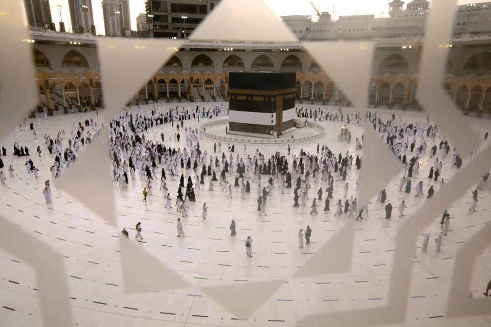 Muslim pilgrims are seen through a glass window as they circumambulate the Kaaba, the cubic building at the Grand Mosque, as they wear masks and keep to social distancing, a day before the annual hajj pilgrimage, Saturday, July 17, 2021. The pilgrimage to Mecca required once in a lifetime of every Muslim who can afford it and is physically able to make it, used to draw more than 2 million people. But for a second straight year it has been curtailed due to the coronavirus with only vaccinated people in Saudi Arabia able to participate. (AP Photo/Amr Nabil)