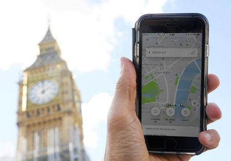FILE PHOTO: A photo illustration shows the Uber app on a mobile telephone, as it is held up for a posed photograph in central London