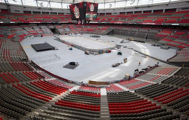 Workers prepare the ice and B.C. Place stadium for the NHL Heritage Classic hockey game in Vancouver, British Columbia, on Wednesday, Feb. 26, 2014. The Vancouver Canucks and the Ottawa Senators are scheduled to play on Sunday at the stadium. (AP Photo/The Canadian Press, Darryl Dyck)