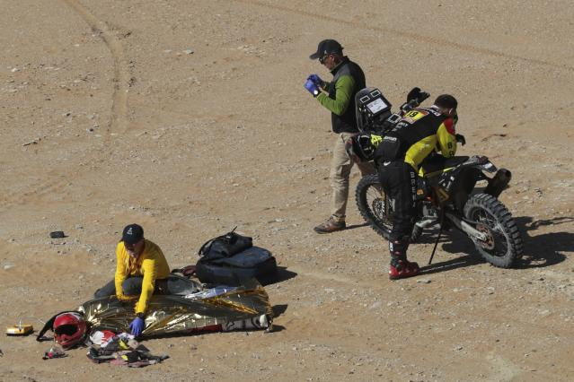 The body of Paulo Gonalves of Portugal is covered with a blanket after a deadly fall during stage seven of the Dakar Rally between Riyadh and Wadi Al Dawasir, Saudi Arabia, Sunday, Jan. 12, 2020. Gonalves, 40, died after an accident with his Hero motorbike. (AP Photo/Bernat Armangue)