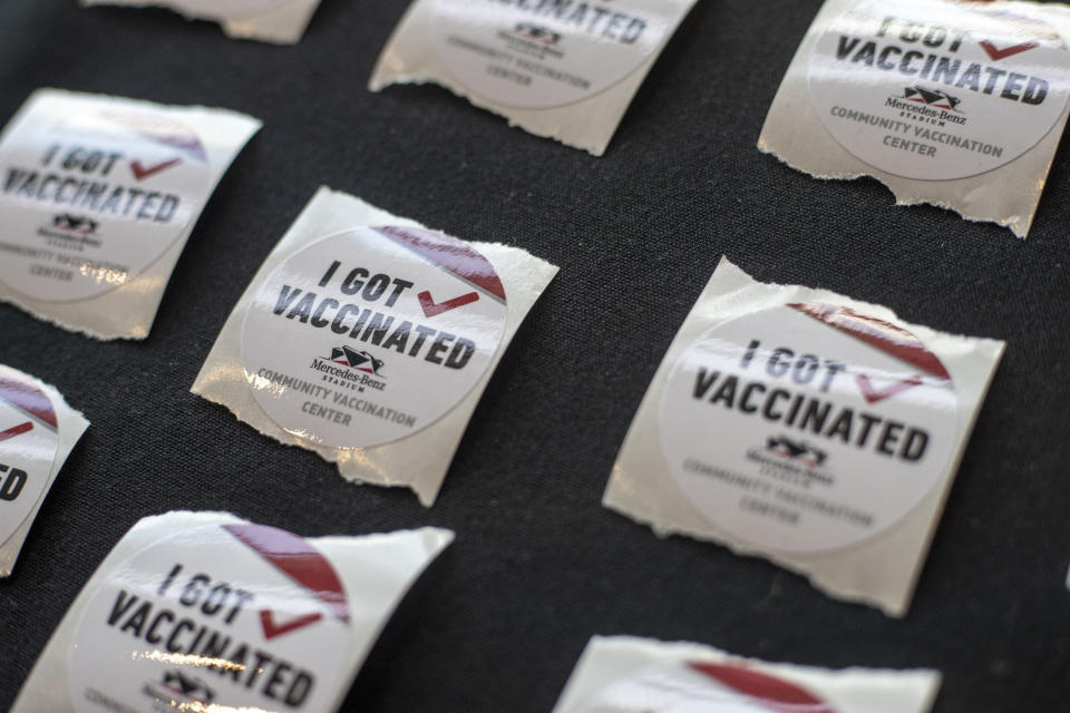 FILE - In this March 30, 2021, file photo, stickers are available for individuals that receive a vaccination at Mercedes-Benz Stadium Community Vaccination Center in Atlanta. The U.S. moved closer Thursday, April 1, toward vaccinating 100 million Americans in a race against an uptick in COVID-19 cases that is fueling fears of another nationwide surge just as the major league baseball season starts and thousands of fans return to stadiums. (Alyssa Pointer/Atlanta Journal-Constitution via AP, File)