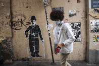A man wearing a face mask, walks by a Charlie Chaplin street art, in the Montmartre district of Paris, Sunday Oct.25, 2020. A curfew intended to curb the spiraling spread of the coronavirus, has been imposed in many regions of France including Paris and its suburbs. (AP Photo/Lewis Joly)