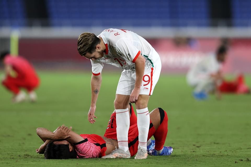 YOKOHAMA, JAPAN - JULY 31: Youngwoo Seol #12 of Team South Korea looks dejected as he is consoled by Ricardo Angulo #19 of Team Mexico following the Men's Quarter Final match between Republic Of Korea and Mexico on day eight of the Tokyo 2020 Olympic Games at International Stadium Yokohama on July 31, 2021 in Yokohama, Kanagawa, Japan. (Photo by Francois Nel/Getty Images)