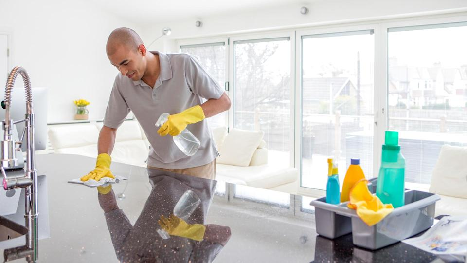 Shot of a young mixed race man cleaning a kitchen top.