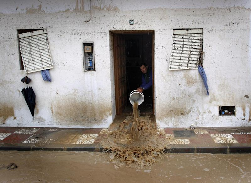 A man to clear muddy water from his house, after heavy rain caused flash floods in the town of Villanueva del Rosario, Malaga, southern Spain, Friday, Sept. 28, 2012. Homes were destroyed and at least one woman was killed. Rescue workers are searching to determine if there are more victims. (AP Photo/Sergio Torres)