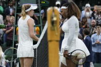 Serena Williams of the US is greeted by Aliaksandra Sasnovich of Belarus, left, at the net after retiring from the women's singles first round match against on day two of the Wimbledon Tennis Championships in London, Tuesday June 29, 2021. (AP Photo/Kirsty Wigglesworth)