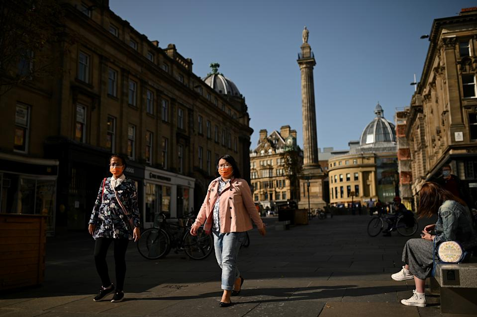 "Pedestrians wearing face masks or coverings due to COVID-19, walk in Newcastle city centre, north-east England, on September 17, 2020. - The British government on Thursday announced new restrictions for northeast England, the latest region to see a surge in coronavirus cases as Prime Minister Boris Johnson warned of a ""second hump"" in nationwide transmission. Residents in the northeast, which includes the cities of Newcastle and Sunderland, will no longer be allowed to socialise outside their own homes or support bubble from Friday onwards. (Photo by Oli SCARFF / AFP) (Photo by OLI SCARFF/AFP via Getty Images)"