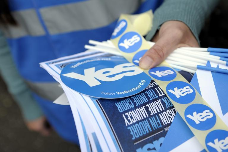 Pro-independence stickers are distributed by supporters outside the Birnam Highland Games in Perthshire, Scotland, on August 30, 2014 (AFP Photo/Andy Buchanan)