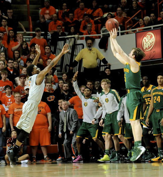 Baylor guard Brady Heslip, right, shoots a 3-point shot over Oklahoma State guard Stevie Clark, left, during the second half of an NCAA college basketball game in Stillwater, Okla., Saturday, Feb. 1, 2014. Heslip scored 20 points in their 76-70 win. (AP Photo/Brody Schmidt)