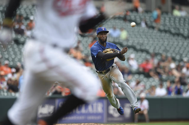 Baltimore Orioles' Adam Jones, left, races to first on a slow ground ball as Texas Rangers' Jurickson Profar throws to first in the seventh inning of a baseball game, Sunday, July 15, 2018, in Baltimore. Jones earned a hit on the play. (AP Photo/Gail Burton)
