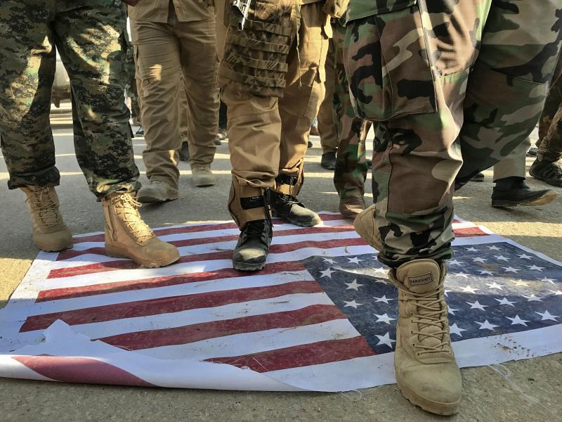 Mourners step over the print of a U.S. flag during the funeral procession of Abu Ali al-Dabi, a fighter of the Popular Mobilization Forces, during his funeral procession in Baghdad, Iraq, Monday, Aug. 26, 2019. Two unidentified drones killed two Iraqi members of an Iran-backed paramilitary force on Sunday, the group said in a statement, saying the attack took place in Iraq near the border with Syria. (AP Photo/Ali Abdul Hassan)