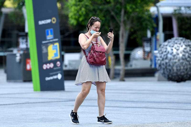 A woman is seen making a video call while wearing a face mask in the CBD of Brisbane.