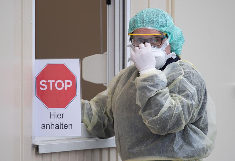 "09 March 2020, Baden-Wuerttemberg, Nürtingen: A hospital employee stands at a container during a press appointment for the start of a ""drive-in"" test station. (to dpa ""First ""Drive-In"" test stations for Coronavirus go into operation"") Photo: Marijan Murat/dpa (Photo by Marijan Murat/picture alliance via Getty Images)"