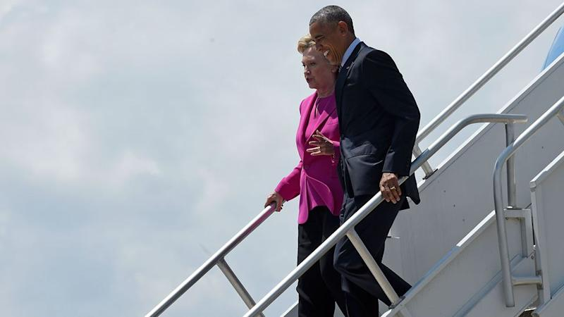 Democratic presidential candidate Hillary Clinton talks to President Barack Obama as they walk down the steps of Air Force One. Photo: AP