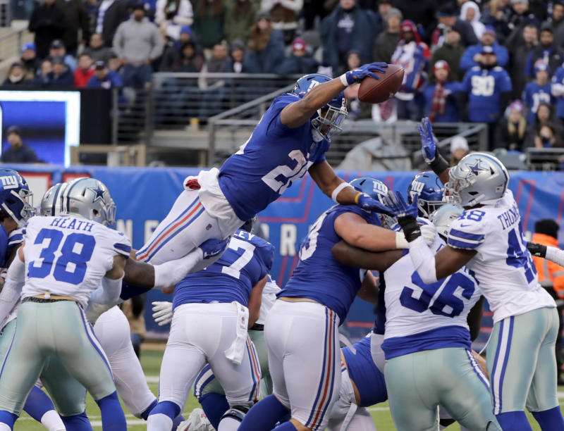 New York Giants' Saquon Barkley, top, scores a touchdown just before the ball is knocked from his hands during the second half of an NFL football game against the Dallas Cowboys, Sunday, Dec. 30, 2018, in East Rutherford, N.J. (AP Photo/Frank Franklin II)