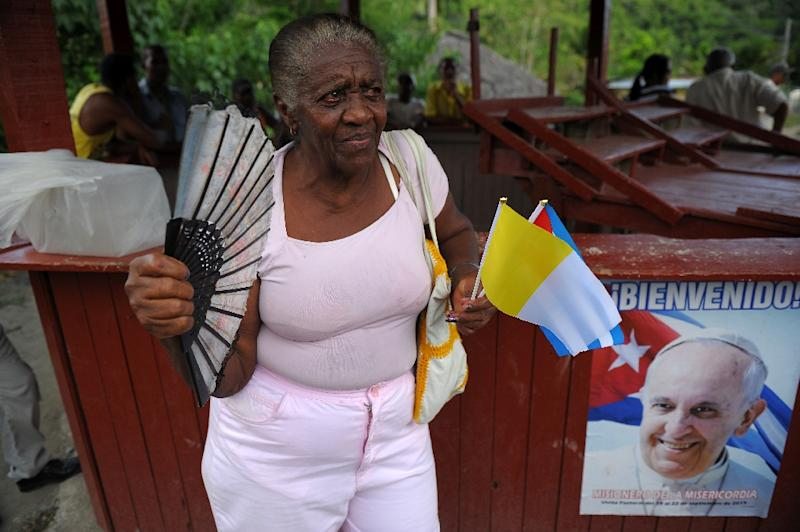 A woman waits for Pope Francis with flags of Cuba and the Vatican in El Cobre, Santiago de Cuba on September 21, 2015 (AFP Photo/Yamil Lage)