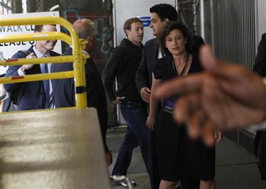 Mark Zuckerberg arrives at New York City's Sheraton Hotel as security guards try to shield him and other Facebook executives from cameras, May 7, 2012.