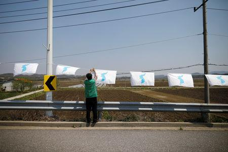 A man hangs a unification flag on the Grand Unification Bridge which leads to the Peace House, the venue for the inter-Korean summit, near the demilitarized zone separating the two Koreas in Paju, South Korea, April 25, 2018.  REUTERS/Kim Hong-Ji/Files