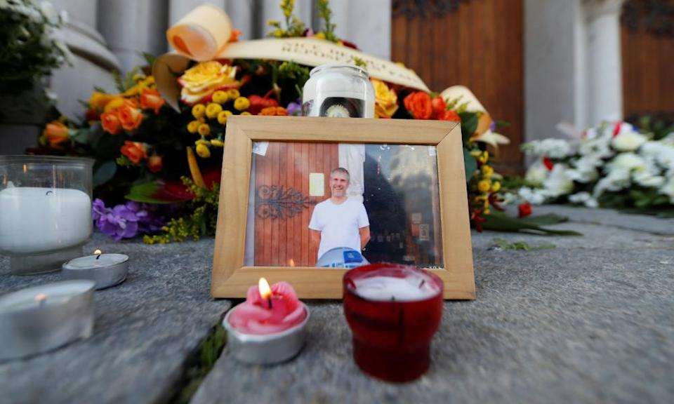 A picture of Vincent Loquès is seen among candles and flowers in front of Notre Dame basilica