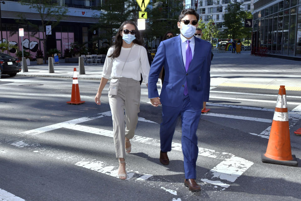 Former Fall River, Mass. Mayor Jasiel Correia, right, and his wife Jenny Fernandes, arrives for a court appearance at the John Joseph Moakley United States Courthouse, Monday, Sept. 20, 2021, in Boston. Correia, who was elected at the age of 23 with promises to rejuvenate the struggling mill city, was scheduled to be sentenced for stealing from investors in a smartphone app he created and extorting hundreds of thousands of dollars in bribes from marijuana businesses. (AP Photo/Josh Reynolds)