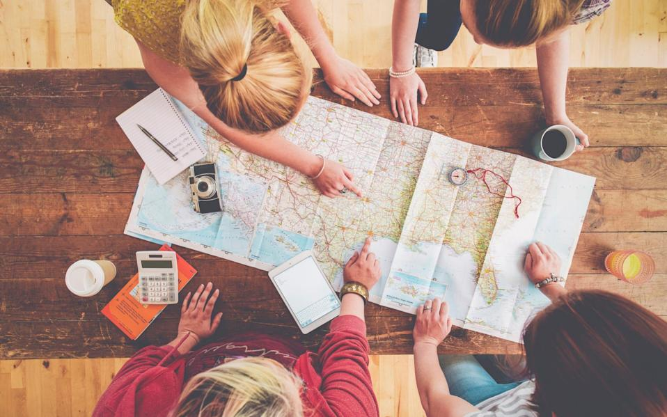 Friends using a map to plan a holiday - Getty