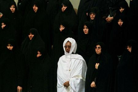 FILE PHOTO: A woman from an African Islamic country (in white) stands among Iranian women during the national anthem of Iran at the opening session of the 8th Islamic Conference Summit in Tehran's new conference building on December 9. REUTERS/Yannis Behrakis/File photo
