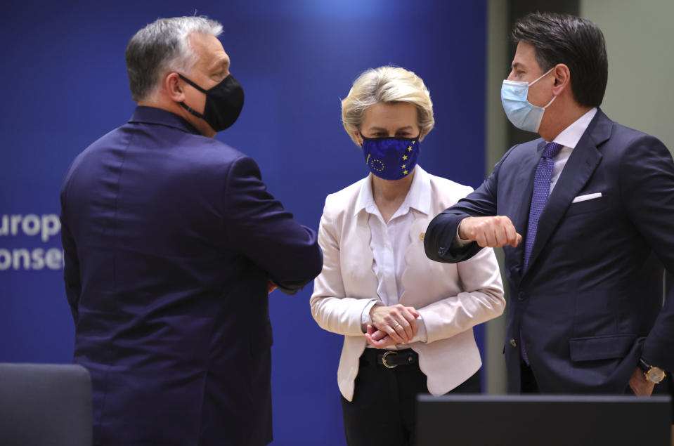 European Commission President Ursula von der Leyen, center, looks on as Hungary's Prime Minister Viktor Orban, left, greets Italy's Prime Minister Giuseppe Conte during a round table meeting at an EU summit in Brussels, Thursday, Dec. 10, 2020. European Union leaders meet for a year-end summit that will address anything from climate, sanctions against Turkey to budget and virus recovery plans. Brexit will be discussed on the sidelines. (AP Photo/Olivier Matthys, Pool)