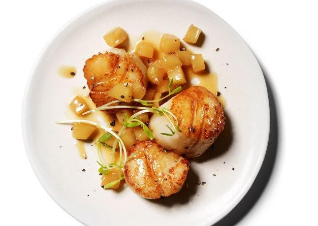 """Granny Smith apples are ideal for this dish: Their sweet-tart juice complements the rich scallops, and they keep their shape when cooked. <a href=""""https://www.bonappetit.com/recipe/scallops-with-apple-pan-sauce?mbid=synd_yahoo_rss"""" rel=""""nofollow noopener"""" target=""""_blank"""" data-ylk=""""slk:See recipe."""" class=""""link rapid-noclick-resp"""">See recipe.</a>"""
