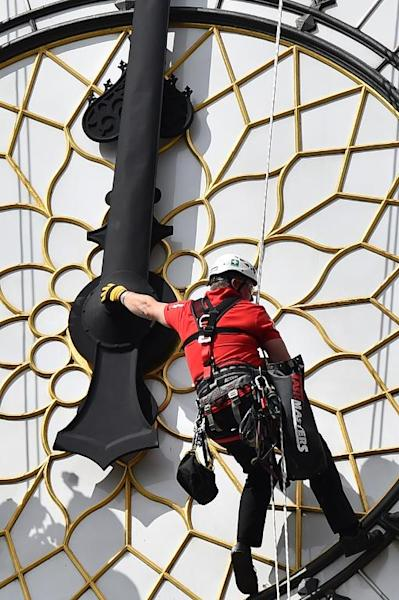 A technician cleans and carries out maintenance work on one of the faces of the Great Clock atop the landmark Elizabeth Tower that houses Big Ben, attached to the Houses of Parliament, in London, on August 19, 2014 (AFP Photo/Ben Stansall)