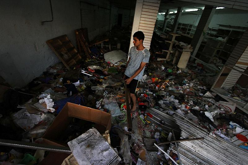 An employee of a looted supermarket inspects the damage in La Fria, Venezuela's Tachira state, in 2016 (AFP Photo/George Castellanos)