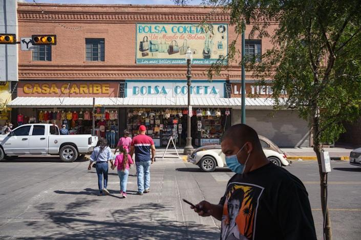 People wearing masks amid the Covid-19 pandemic are pictured on October 24, 2020 in downtown El Paso, Texas.