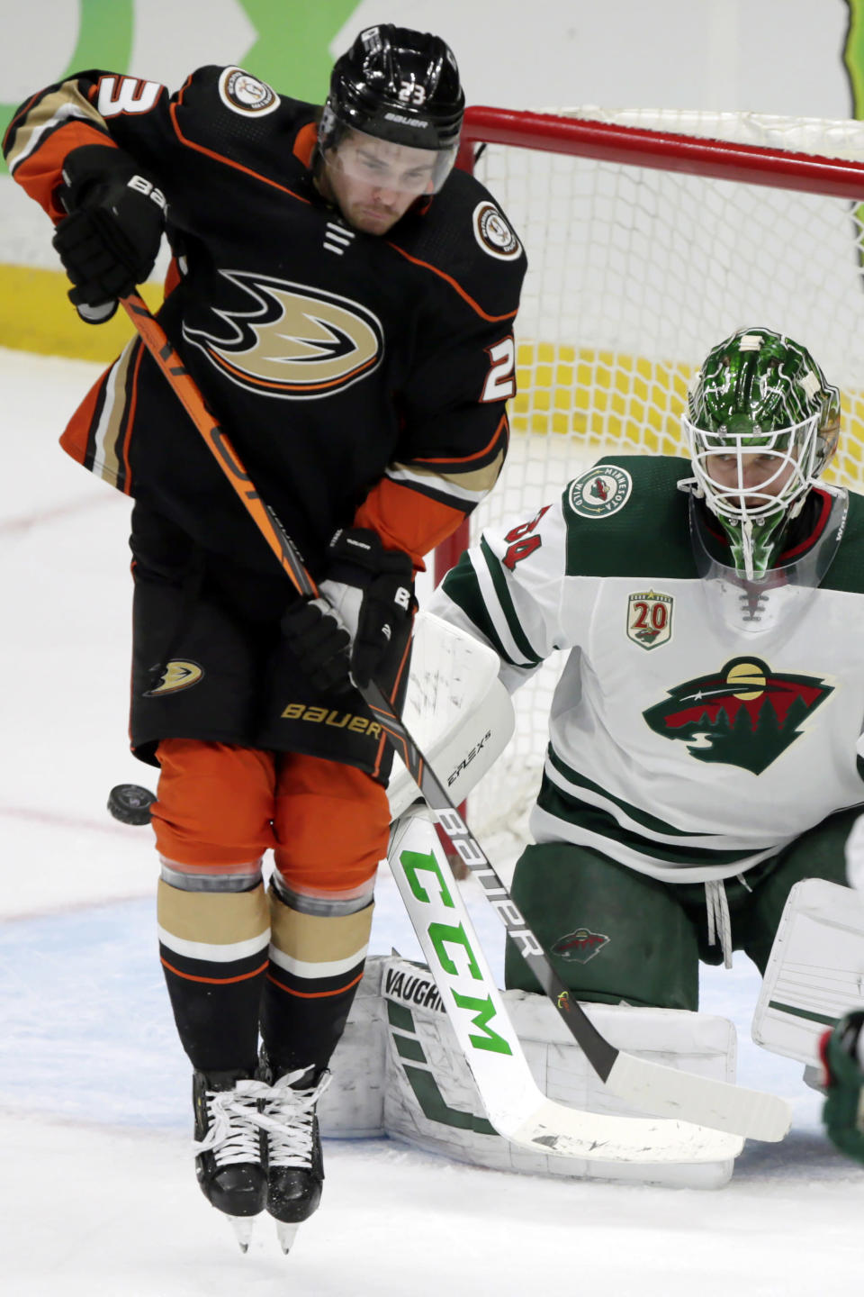 Anaheim Ducks center Sam Steel, left, shields Minnesota Wild goaltender Kaapo Kahkonen as the puck sails wide of the goal during the first period of an NHL hockey game in Anaheim, Calif., Wednesday, Jan. 20, 2021. (AP Photo/Alex Gallardo)