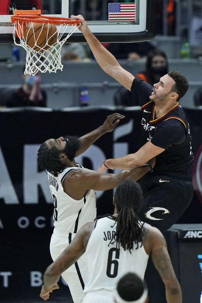 Cleveland Cavaliers' Larry Nance Jr., right, dunks the ball against Brooklyn Nets' James Harden in the second half of an NBA basketball game, Friday, Jan. 22, 2021, in Cleveland. The Cavaliers won 125-113. (AP Photo/Tony Dejak)