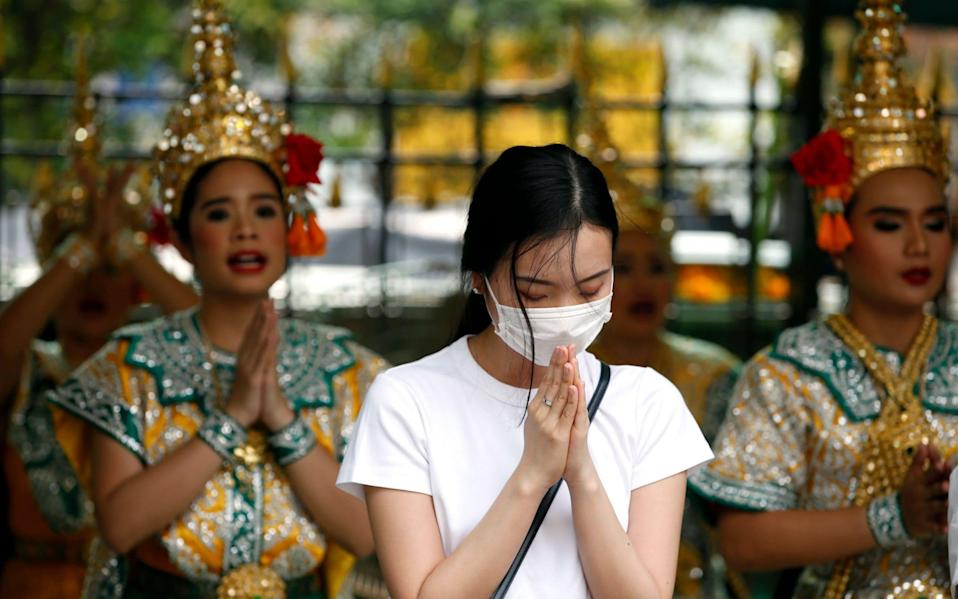 A worshipper wearing protective mask offers prayers in Bangkok after Thai health official confirmed its found two cases of coronavirus - REX