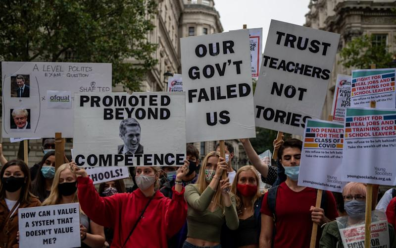 Students, teachers and parents hold placards and wear face masks as they protest against downgraded A level results due to Covid-19 - Chris J Ratcliffe/Getty Images Europe
