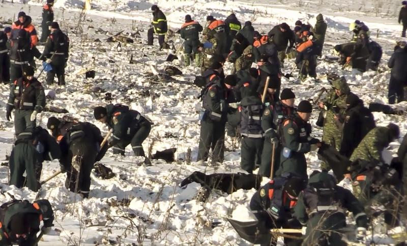 In this photo provided by the Russian Emergency Situations Ministry, Emergency teams work at the scene of a AN-148 plane crash in Stepanovskoye village, about 40 kilometers (25 miles) from the Domodedovo airport, Russia, Monday, Feb. 12, 2018. Emergency teams combed the snowy fields outside Moscow on Monday, searching for debris from a crashed Russian airliner and the remains of the 71 people aboard it who died. The An-148 twin-engine regional jet bound for Orsk in the southern Urals went down minutes after taking off from Moscow's Domodedovo airport Sunday afternoon. All 65 passengers and 6 crew on board were killed. (Russian Ministry for Emergency Situations photo via AP)