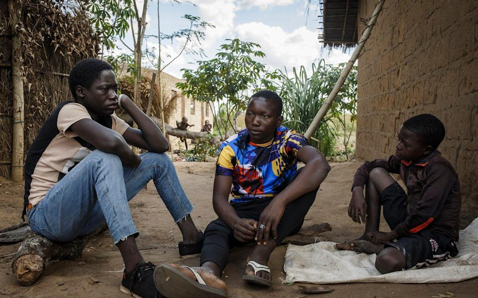 Julio (on the felt) next to his friend and little brother (on the right) outside their foster home in Cabo Delgado. - Ed Ram