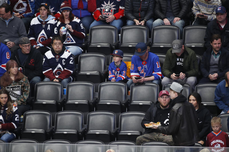 Empty seats are seen in the lower bowl of Pepsi Center as the Colorado Avalanche play the New York Rangers in the first period of an NHL hockey game Wednesday, March 11, 2020, in Denver. (AP Photo/David Zalubowski)