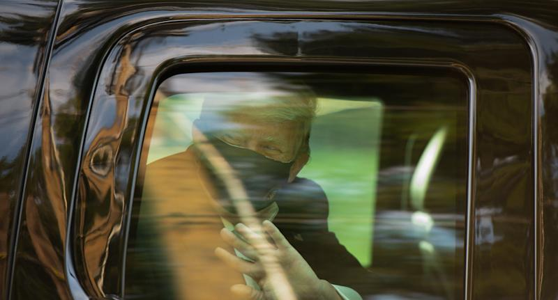 Donald Trump waving from a car wearing a mask