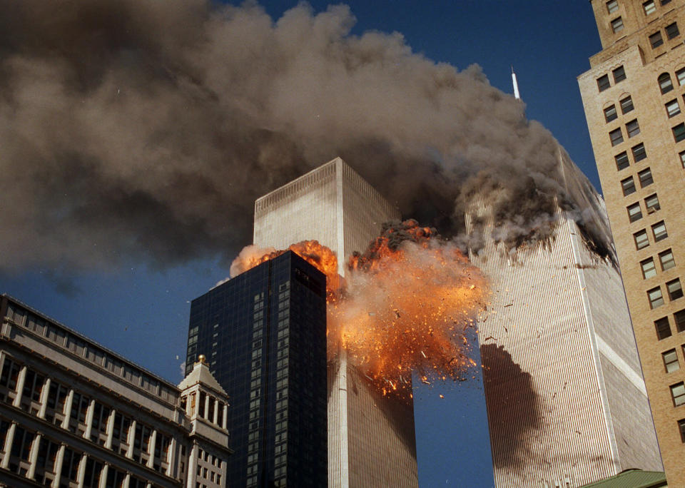 Smoke billows from one of the towers of the World Trade Center as flames and debris explode from the second tower, Tuesday, Sept. 11, 2001. (AP Photo/Chao Soi Cheong)