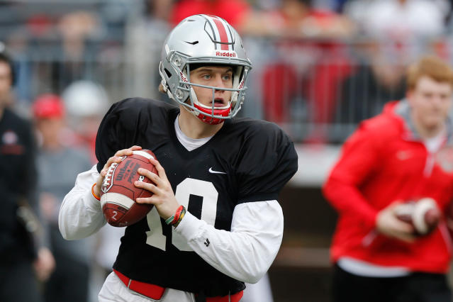 FILE - In this April 14, 2018, file photo, Ohio State quarterback Joe Burrow drops back to pass during an NCAA college spring football game in Columbus, Ohio. Facing the possibility of sitting as a backup for a third season at Ohio State, quarterback Joe Burrow announced on Tuesday, May 8, 2018, his intention to transfer. The news from the redshirt junior, delivered via Twitter, wasnt unexpected. (AP Photo/Jay LaPrete, File)