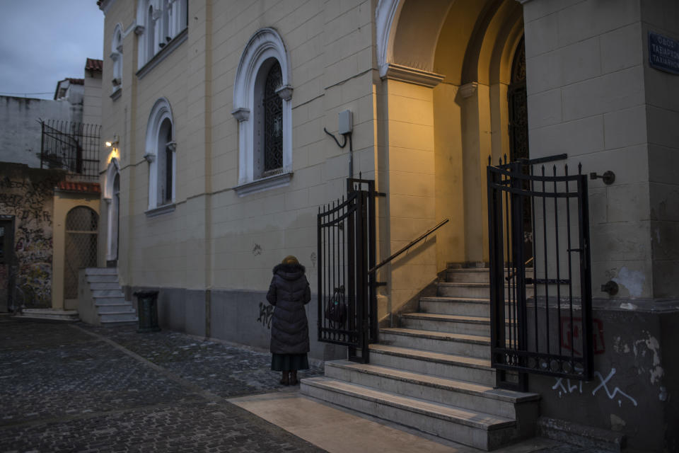 A woman prays outside an Orthodox Church in the Monastiraki district of Athens, on Sunday Dec. 20, 2020. Despite six weeks of lockdown measures, coronavirus deaths and infections remain high, piling pressure on the country's health system.(AP Photo/Petros Giannakouris)