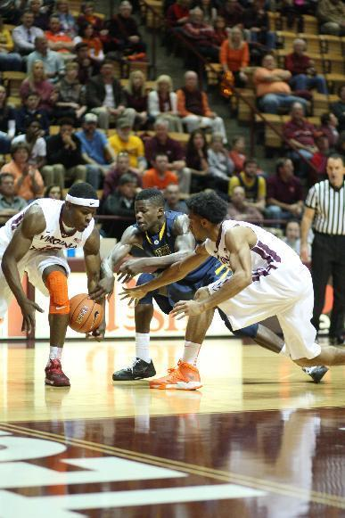 From left, Virginia Tech guard Ben Emelogu (15), West Virginia guard Eron Harris (10), and Virginia Tech guard Adam Smith (3) dive for a loose ball during the first half of an NCAA college basketball game in Blacksburg, Va., Tuesday, Nov. 12, 2013. (AP Photo/The Roanoke Times, Daniel Lin)