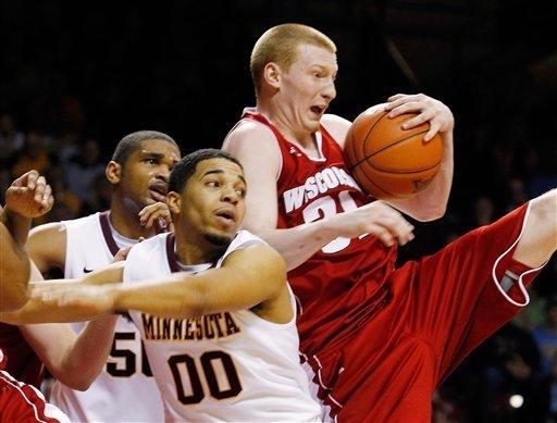 Wisconsin's Mike Bruesewitz (31), right, pulls down a rebound against Minnesota's Julian Welch (00) during overtime of an NCAA college basketball game Thursday, Feb. 9, 2012, in Minneapolis. Wisconsin defeated Minnesota 68-61. (AP Photo/Genevieve Ross)