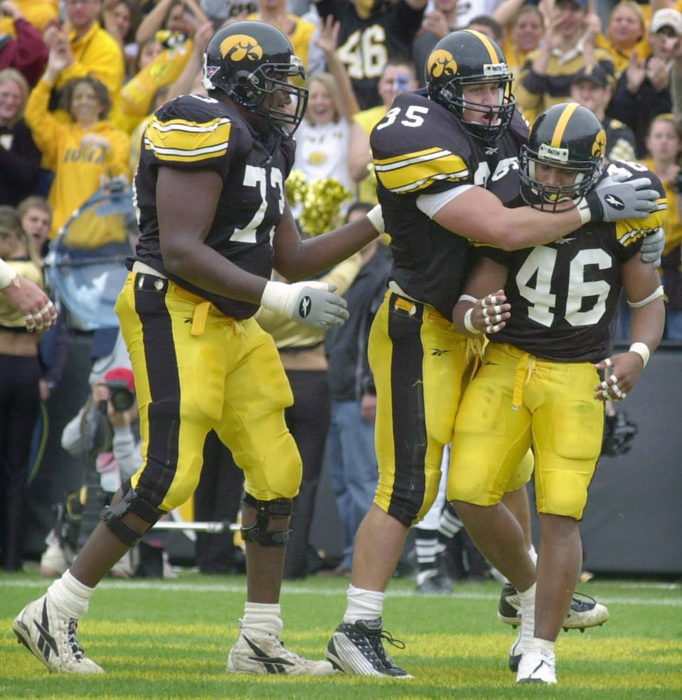 FILE - In this Saturday, Sept. 29, 2001, file photo, Iowa's Ladell Betts (46) celebrates with teammates Erik Jensen, center, and David Porter, left, after scoring a touchdown against Penn State during the first half of an NCAA college football game in Iowa City, Iowa. Ladell Betts says Iowa City has changed a lot in the 20 years since he wrapped up his college career, what with all the new housing areas, hotels, coffee shops and restaurants. As for the Iowa football program, he says, it was like stepping back in time when he arrived this spring as the new running backs coach. (AP Photo/Charlie Neibergall, File)